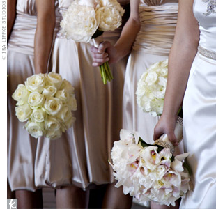 The bridesmaids dressed in champagne-colored dresses with ruching and a trendy bubble hem by Dessy. Each bridesmaid carried a different bouquet in a single cream-colored bloom, ranging from roses, peonies, ranunculus, lisianthus, tulips, cymbidium orchids, hydrangeas, and mini calla lilies