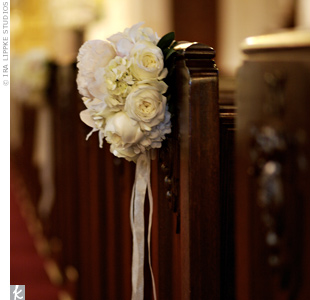 Simple bouquets of ivory peonies, roses, and hydrangeas adorned every other pew.