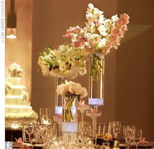Three cylinder vases were filled with LED light cubes and sea glass, and topped off with blush cymbidium orchids, cream peonies, and white hydrangeas, lisianthus, and roses.