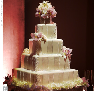 Mimicking the embroidery on the bride's train, the four-tiered cake had alternating matte and pearl stripes with blush cymbidium orchids. For an even more luxurious touch, the cake rested on a platform of sparkling rhinestones.