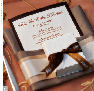 Copper linens draped the tables while each setting was decorated with an olive, copper, and champagne napkin, topped with the menu and a white mini photo album.