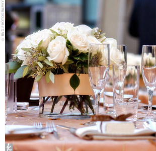 Modern square glass vases overflowed with romantic white roses and fern curls.
