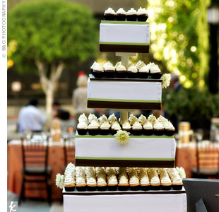 In lieu of a cake, mini cupcakes lined a tiered stand decorated with chocolate brown and olive ribbon and pale yellow mums.