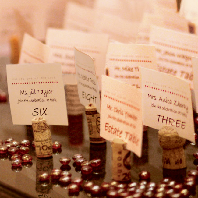 The escort cards featuring red polka dots were placed in corks and scattered on an antique marble table. At the same table was a framed collage of the couple's childhood pictures.