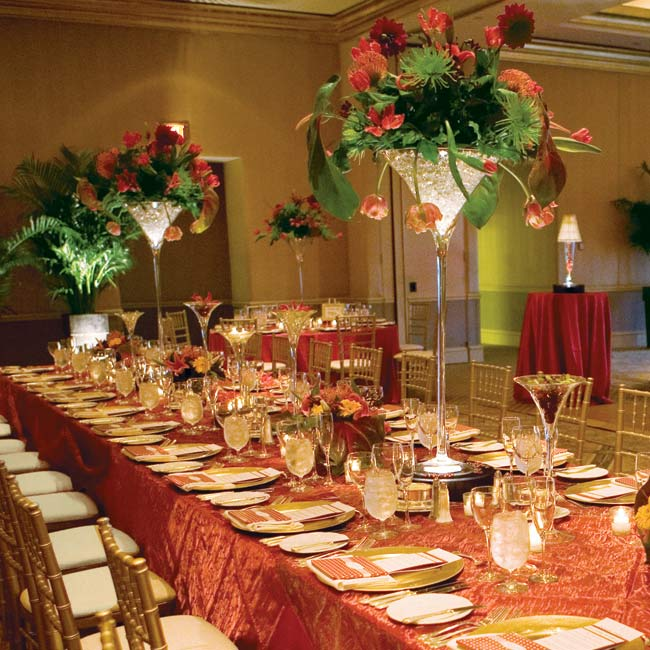 Floral centerpieces comprised of martini glasses and short square vases graced the long elegant tables. Each centerpiece was filled with exotic flowers and surrounded by small glass candle votives.