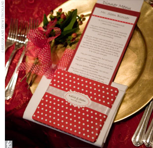 The reception tables were set with red table linens and gold chargers. White and red menus were tucked inside white napkins with homemade CD favors wrapped in red and white, polka dot paper sitting on top.