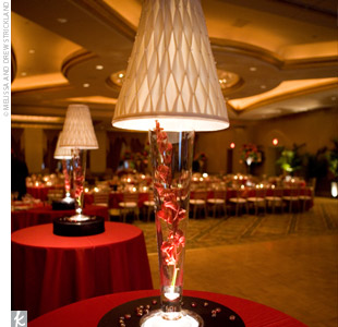 Tall tables, covered in red linens and topped with candle lamps filled with red orchids, surrounded the dance floor.