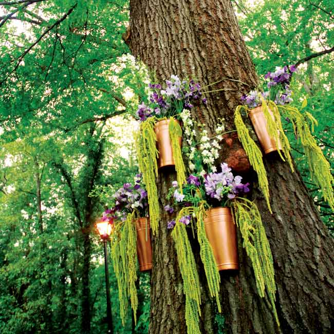 During the ceremony, the tree that stood behind the couple was decorated with copper pots filled with purple sweet pea, white larkspur, and green hanging amaranthus.
