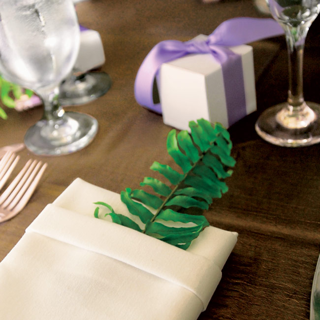 The reception tables were set with white linens and green silk toppers. At each place setting was a napkin folded into a pocket shape and accented with a fern leaf.