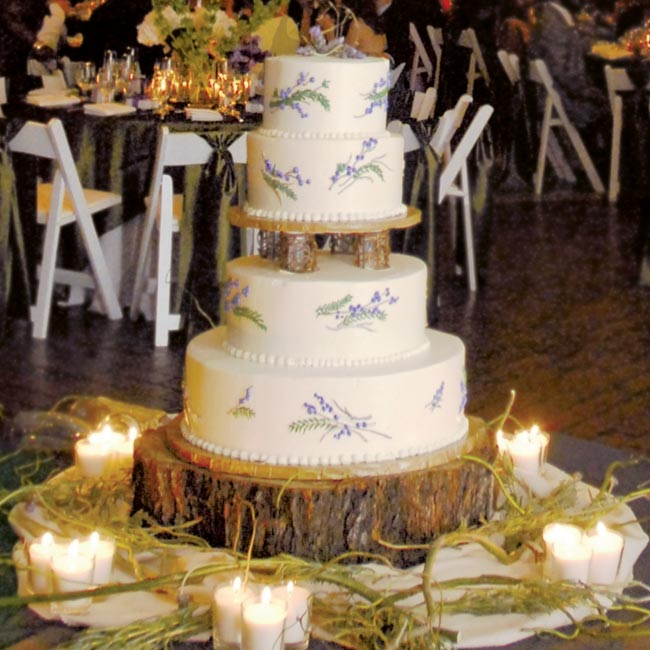 Natasha and Christopher's four-tiered buttercream cake was frosted with an ivory twig and purple berry design. A tree trunk served as the cake stand, and curly willow and fresh lavender topped off the confection.