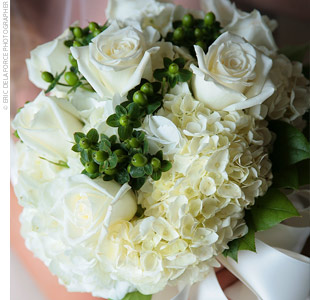 Anna carried a cream-colored bouquet of hydrangeas and roses accented with green hypericum berries. The stems were tied off with a white silk ribbon.
