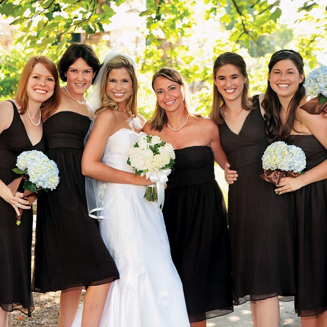 Anna's five bridesmaids wore black knee-length dresses in various styles from J.Crew and carried clusters of blue hydrangeas, which were hand-tied with brown ribbon.