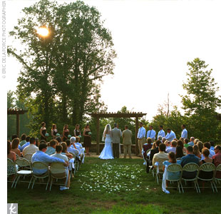 Anna and Chris&#39; ceremony took place on a large lawn outside the resort. The couple stood beneath an arbor overlooking the mountains at sunset.