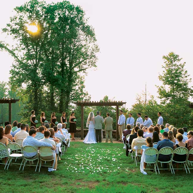 Anna and Chris' ceremony took place on a large lawn outside the resort. The couple stood beneath an arbor overlooking the mountains at sunset.