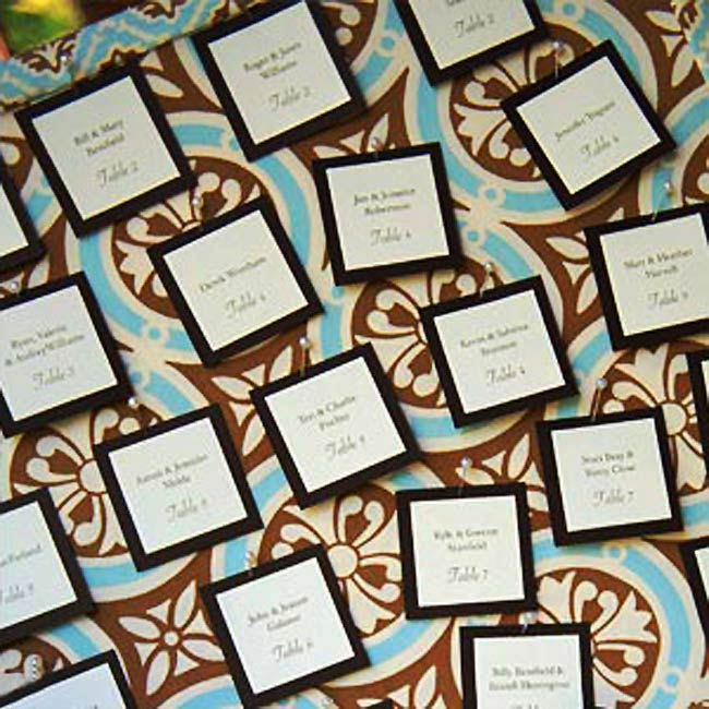 Anna created the escort cards and pinned them to a giant bulletin board, which was covered in the same fabric used for the table runners. Chris' mother made small pincushions out of the same fabric so that guests had a place to put their pins after removing their cards.