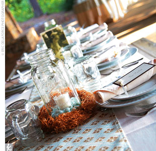 The tables at Anna and Chris&#39; reception were covered in brown and blue-patterned fabric. In lieu of flowers, the couple used candles in mason jars as centerpieces.