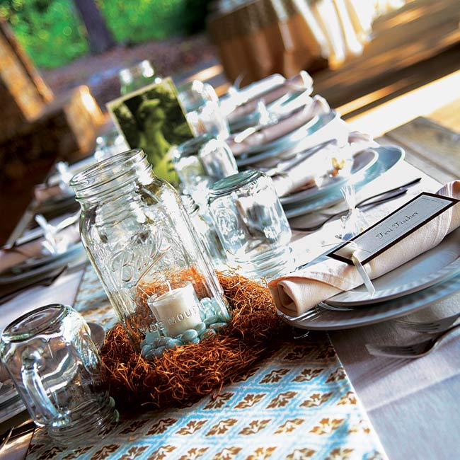 The tables at Anna and Chris' reception were covered in brown and blue-patterned fabric. In lieu of flowers, the couple used candles in mason jars as centerpieces.