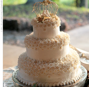 Anna and Chris&#39; wedding cake was a three-tiered confection covered in white buttercream and topped with white sugar flowers. A decorative birdcage with two lovebirds served as a cake topper.