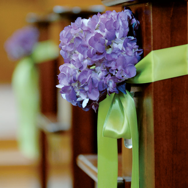 Deep purple hydrangeas were tied to the church's aisle pews with green silk ribbon.