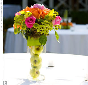 Apple-filled vases bursting with lime green button mums, pink and mango roses and pink peonies created a simple spring look.