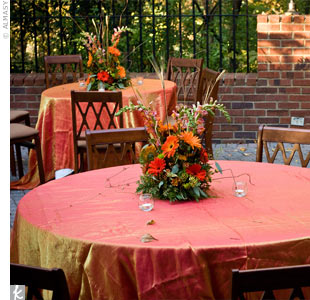 Overflowing arrangements of burnt orange, copper and moss green daisies, orchids, snapdragons and hypericum berries decorated each table.