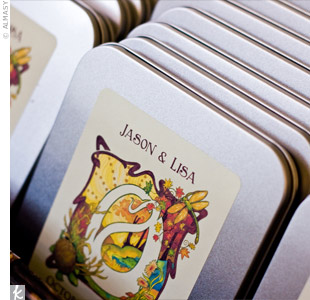 Green CDs with custom-made caricatured labels of the couple sat in silver tins labeled with stickers printed with the couple's name and wedding date.