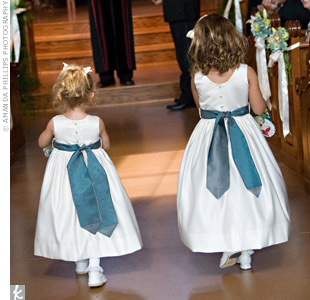 Blue sashes added a touch of color to the flower girl's white, sleeveless dresses.