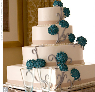 Blue sugar flowers connected by silver fondant twigs cascaded down the four-tiered, ivory cake.