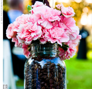 Mason jars filled with coffee beans and pink carnations hung from Shepard's hooks along the aisle.