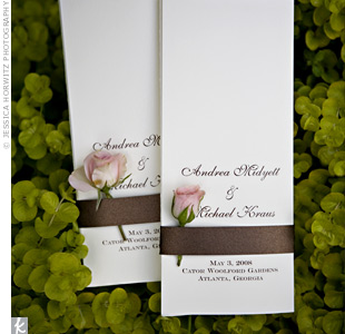 Brown ribbon tied together the cream tri-fold programs. Each was accented with a garden rose.