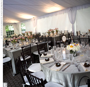 The reception took place under a white tent. Round and square tables were covered with silver linens and surrounded by black chivari chairs.