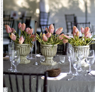 Three gray urns filled with pink tulips rested on the square tables.