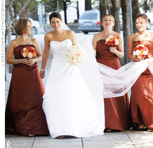 Hand-tied bouquets of burnt orange and cream roses complemented the bridesmaid's cinnamon-colored, floor-length gowns.