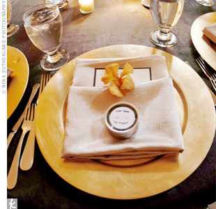 Beige napkins with orange orchids tucked inside topped gold chargers.