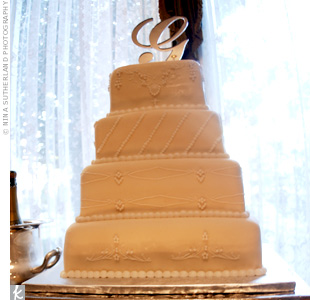 "Inspired by her beaded gown, the bride designed a four-tiered, ivory-frosted cake with the same pattern. A silver ""G"" topped it off."