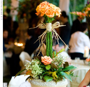 Smaller arrangements of fall-colored roses, hydrangeas, and mums were placed inside antique-style urns and surrounded by votive candles.
