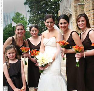 The bridesmaid&#39;s mango calla lily bouquets popped against their chocolate brown, tea-length dresses with champagne sashes by Ann Taylor.