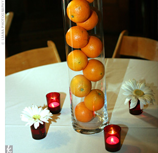 For a clean look, cylinder vases filled with oranges topped the cream tablecloths.