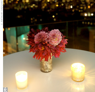 Vintage-inspired vases filled with bold red and pink blooms were surrounded by simple votive candles.