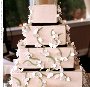 Fondant branches, leaves and flowers decorated the four-tiers of the square buttercream covered cake.