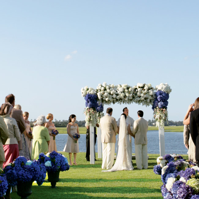 Alex and John's ceremony took place in a grassy area behind the Yacht Club's pool, which overlooks the inlet for a small marina near the Intercoastal Waterway. A gorgeous trellis with blooms in ivory, champagne, and white hues served as the altar.