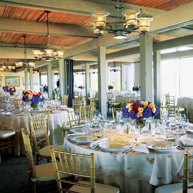 The couple kept the decor simple with white linens and gold chairs, while the centerpieces provided bright bursts of color. The chandeliers hanging above the guests immersed them in candlelight, and the floor-to-ceiling windows offered amazing views of the locale.