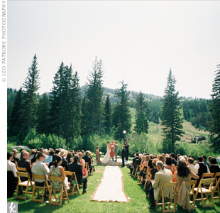 "Nicole and Tyler's outdoor ceremony had a laidback, natural vibe. The decor was simple -- gorgeous mountains provided the view and guests sat on wooden chairs. A classical guitarist enhanced the natural ambience by playing songs like ""Over the Hills and Far Away,"" ""Here Comes the Sun,"" and ""With a Little Help from My Friends."""