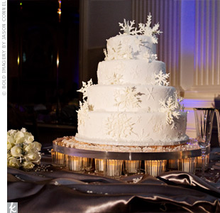 Guests enjoyed Heather and Michaels white, four-tiered cake that featured an elegant snowflake design. Sugar snowflakes and a dusting of edible glitter topped off the wintry cake.