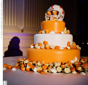 The grooms cake was covered in orange and white fondant -- a nod to Heather and Michaels native Knoxville Tennessee Volunteers -- the couples favorite football team. The confection was topped with a football helmet and surrounded by orange and white Reeses Pieces and miniature chocolate footballs.