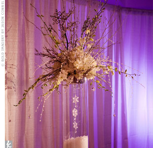 Heather and Michael used two different styles of centerpieces. The taller centerpieces featured the same arrangements used earlier in the ceremony. Each of the tall, clear vases had faux snow at the bottom and a string of snowflakes hanging down the center. The vases were topped with white hydrangeas, iced branches, sprays of crystals, snowflakes,  ...