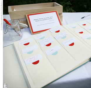 A robin's egg blue guest book with pockets marked in red and blue allowed guests to write personal notes to the couple and tuck them into the pouches.
