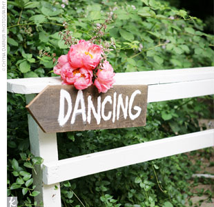 A wooden arrow decorated with pink peonies guided guests to the indoor dance area.