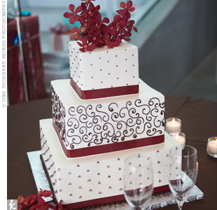 The three-tiered cake had two flavors: triple chocolate and white chocolate raspberry. It featured intricate scrollwork, red ribbons on each tier, and red flowers to top off the look.