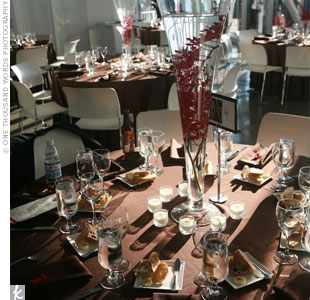 Surrounded by twinkling votive candles, tall, narrow vases were filled with sprays of red orchids submerged in water. The tables were draped in chocolate linens, and the table cards featured the couple's childhood photographs.